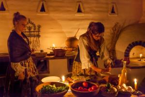 Brittany Avila, left, with Anne Petersen, preparing a historical meal in the Presidio Cocina at a recent living history event.