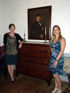 Anne Petersen and Mabel Cobo Hernando stand with the portrait of Jose de la Guerra in the sala of Casa de la Guerra. Photo by Alex Grzywacki
