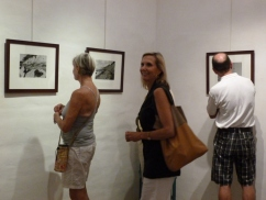 Visitors admiring Shaw's images on opening night. Photo by Mika Thornburg.