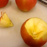 Displacing the apple core by cutting around the core with a knife. Photo by Brittany Avila.
