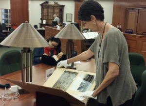 Rose Thomas reviews the Reginald Johnson scrapbooks at the Huntington Library. Photo by Anne Petersen.