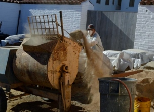 Isidro Ruiz adding screened soil to the mixer to make mortar. Photo by Mike Imwalle.