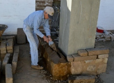 Tim Aguilar spreading mud mortar on the sandstone foundation. Photo by Mike Imwalle.