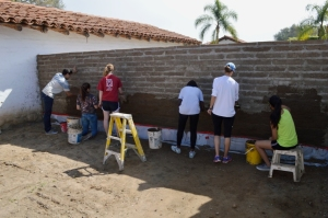 Students applying mud plaster to adobe garden walls at the Northwest Corner complex. Photo by Mike Imwalle.