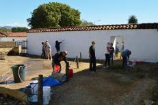 Volunteers whitewashing the back wall of the Comandancia. Photo by Mike Imwalle.